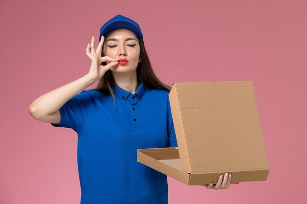 ピンクの壁に空の食品配達ボックスを保持している青い制服と岬の正面図若い女性の宅配便