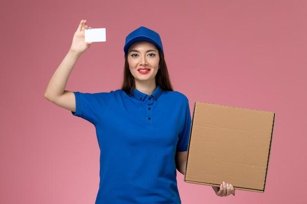 Вид спереди молодая женщина-курьер в синей форме и накидке, держащая коробку с едой и карточку, улыбаясь на розовой стене