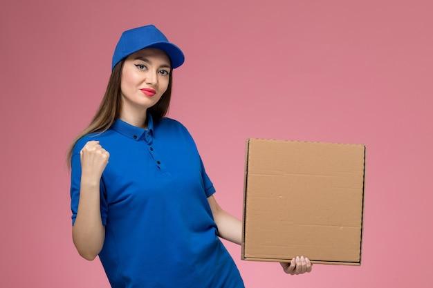 Молодая женщина-курьер в синей форме и плаще, держащая коробку для доставки еды на светло-розовой стене, вид спереди