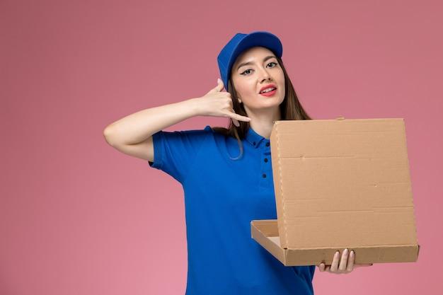 Вид спереди молодая женщина-курьер в синей форме и плаще, держащая коробку для доставки еды, позирует на розовой стене