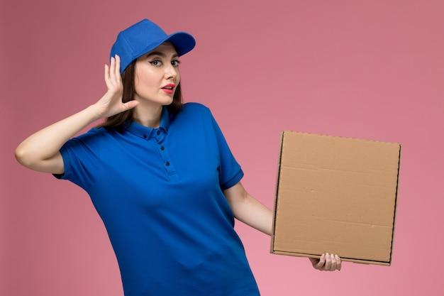 Вид спереди молодая женщина-курьер в синей форме и плаще, держащая коробку для доставки еды, пытается услышать на розовой стене