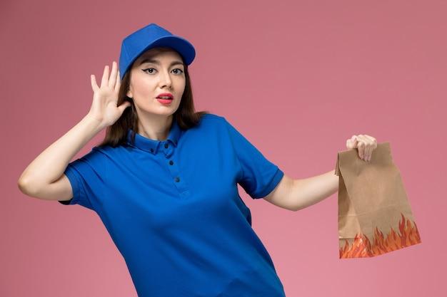 Вид спереди молодая женщина-курьер в синей форме и плаще, держащая бумажный пакет с едой, пытается услышать на розовом столе