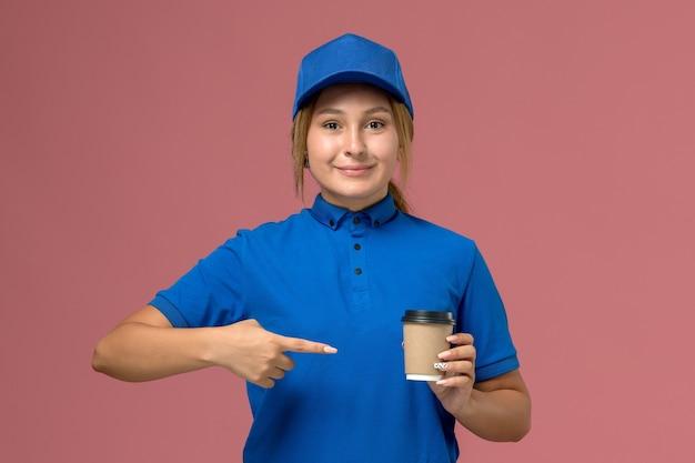 ピンクの壁にコーヒーの配達カップをポーズして保持している青い制服を着た若い女性の宅配便の正面図、サービス制服配達女性の仕事