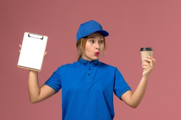 コーヒーとメモ帳のカップを保持している青い制服ポーズの正面図若い女性の宅配便、サービス制服配達女性労働者