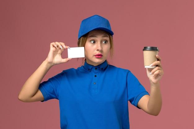Вид спереди молодая женщина-курьер в синей форме позирует, держа чашку кофе и белую карточку, работница службы доставки униформы