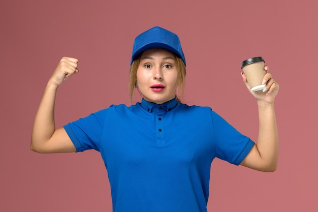 正面図青い制服の若い女性の宅配便は、コーヒーの屈曲を保持しているポーズ、サービス制服配達女性の仕事の労働者