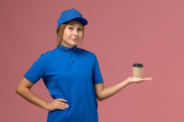 ピンクの壁のサービスの仕事の制服の配達の女性にコーヒーの配達カップを保持している青い制服のポーズで若い女性の宅配便