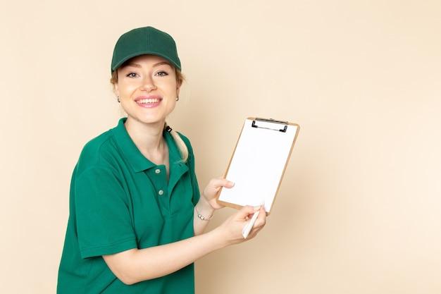 Вид спереди молодая женщина-курьер в зеленой форме и зеленой накидке держит блокнот, улыбаясь на светлой космической работе