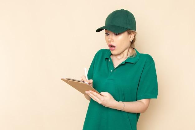 Вид спереди молодая женщина-курьер в зеленой форме и зеленой накидке держит блокнот, пишущий на светлой космической работе