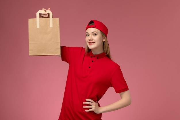 Вид спереди молодая женщина-курьер в красной форме и накидке, держащая посылку с доставкой на розовой стене