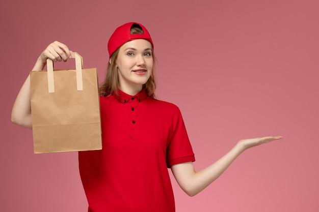 빨간색 유니폼과 케이프 핑크 벽에 배달 음식 패키지를 들고 전면보기 젊은 여성 택배