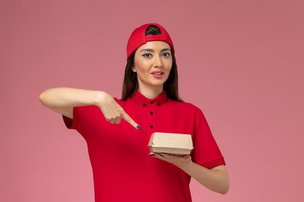 분홍색 벽에 그녀의 손에 작은 배달 음식 패키지와 빨간 유니폼과 케이프 전면보기 젊은 여성 택배
