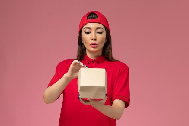 Вид спереди молодая женщина-курьер в красной форме и плаще с маленьким пакетом продуктов для доставки на руках, открывающим его на светло-розовой стене