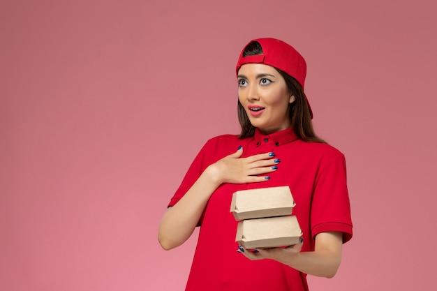 Вид спереди молодая женщина-курьер в красной форме и плаще с небольшими пакетами еды для доставки на руках на розовой стене