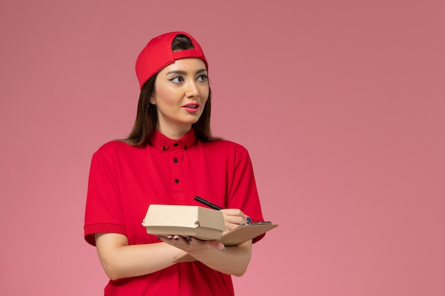 Вид спереди молодая женщина-курьер в красной униформе с небольшим пакетом еды для доставки и блокнотом на руках на светло-розовой стене