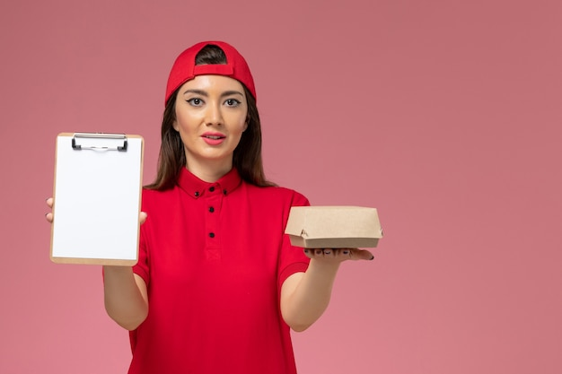 ピンクの壁に彼女の手に小さな配達食品パッケージとメモ帳を備えた赤い制服ケープの正面図若い女性の宅配便