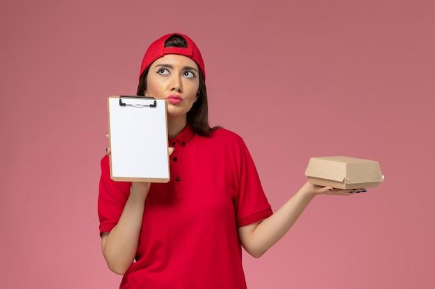 Вид спереди молодая женщина-курьер в красной униформе с небольшим пакетом еды для доставки и блокнотом на руках, думая о розовой стене