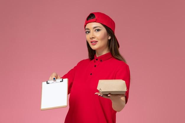 Молодая женщина-курьер в красной форменной накидке, вид спереди с небольшим пакетом еды для доставки и блокнотом с ручкой на руках на светло-розовой стене