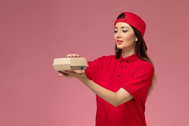 Вид спереди молодая женщина-курьер в красной форме и накидке с небольшим пакетом продуктов для доставки на руках на светло-розовой стене