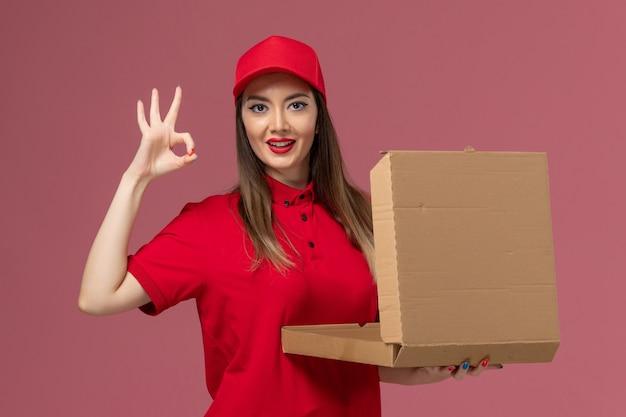 ピンクの背景に配達フードボックスの開口部を保持している赤い制服の正面図若い女性の宅配便配達仕事の制服会社