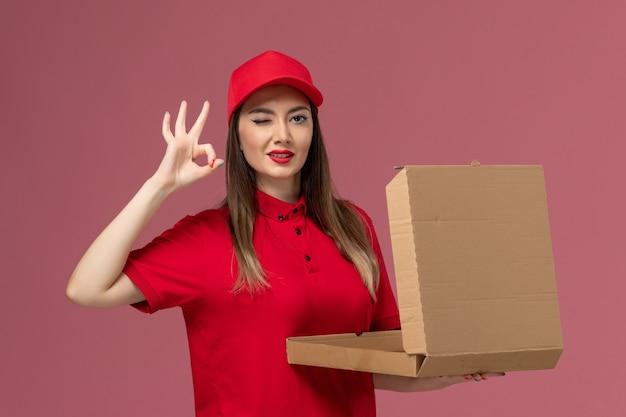 ピンクの背景にポーズをとって配達フードボックスを保持している赤い制服の正面図若い女性の宅配便配達仕事制服会社