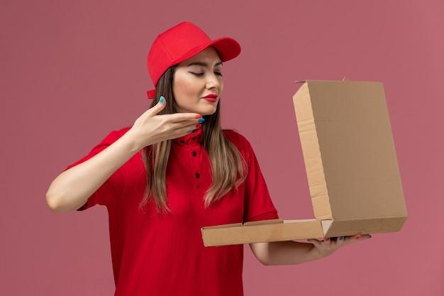淡いピンクの背景に臭いがする配達フードボックスを保持している赤い制服の正面図若い女性宅配便