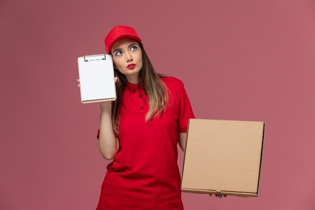 ピンクの背景の配達サービスの制服会社を考えているメモ帳と配達フードボックスを保持している赤い制服の正面図若い女性の宅配便