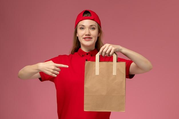 Вид спереди молодая женщина-курьер в красной форме, держащая бумажный пакет с едой на светло-розовой стене