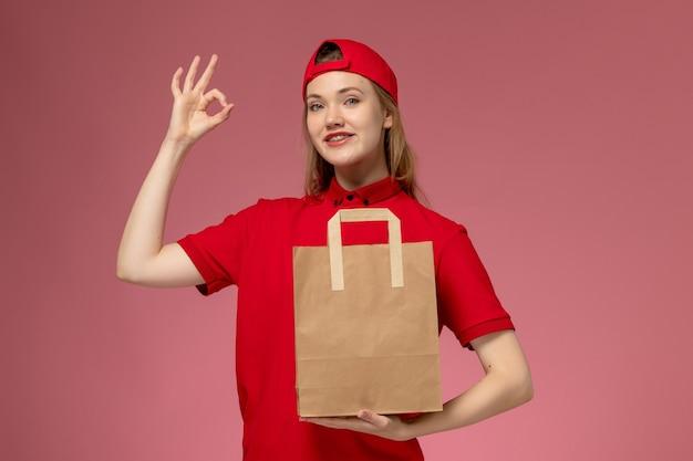 淡いピンクの壁に配達紙食品パッケージを保持している赤い制服を着た若い女性の宅配便の正面図