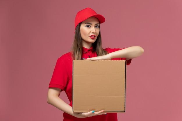 Вид спереди молодая женщина-курьер в красной форме держит коробку с едой на розовом фоне.