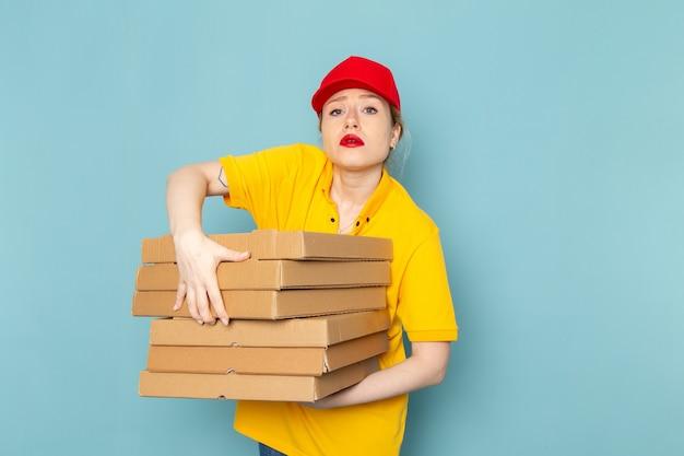 黄色のシャツと赤いマントの青い宇宙の仕事にパッケージを保持している正面若い女性宅配便