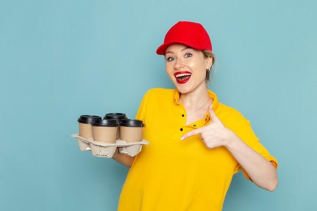 黄色のシャツと青いスペースの仕事にプラスチック製のコーヒーカップを保持している赤いマントの正面の若い女性宅配便