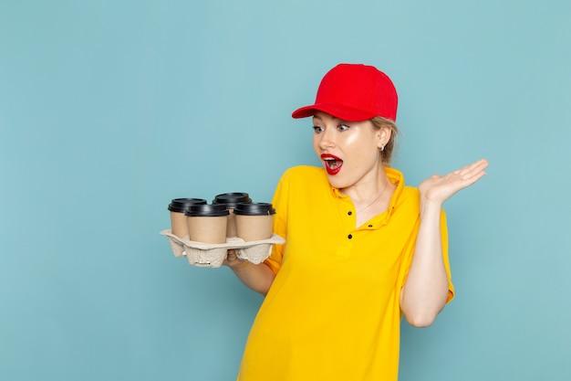 Вид спереди молодая женщина-курьер в желтой рубашке и красной накидке с пластиковыми кофейными чашками на синем космосе.