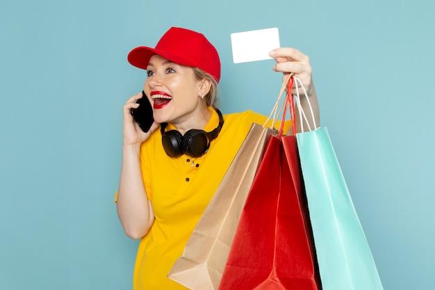 黄色のシャツと赤いマントの青いパッケージの仕事で電話で話しているショッピングパッケージカードを保持している正面若い女性宅配便