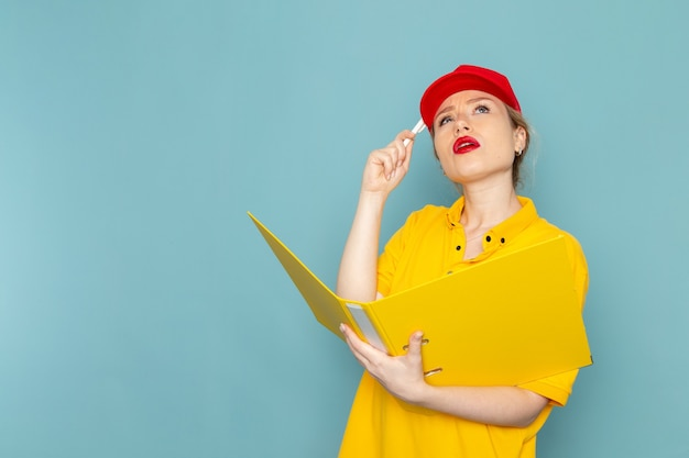 黄色のシャツと赤いマントの青い宇宙労働者の黄色のファイル思考を保持している正面若い女性宅配便
