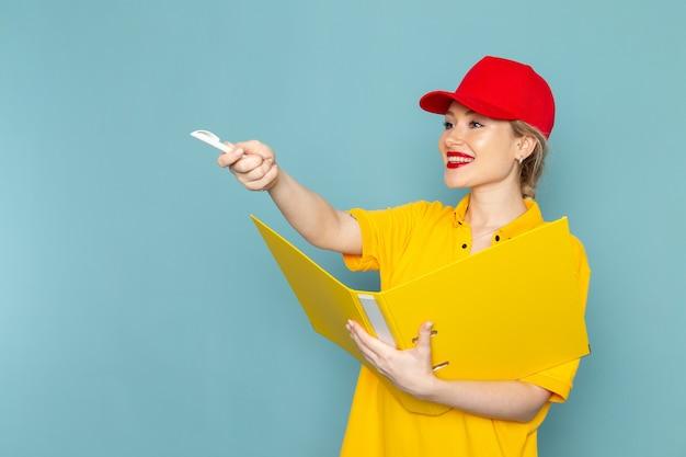 黄色のシャツと赤いマントの青い宇宙の仕事にメモを書き留めて黄色のファイルを保持している正面若い女性宅配便