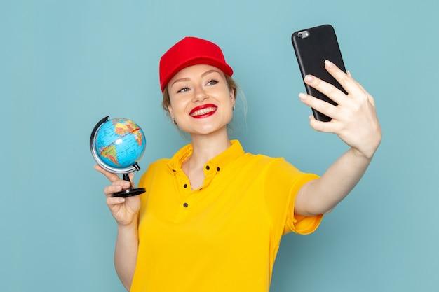 Молодая женщина-курьер в желтой рубашке и красной накидке, делающая селфи с глобусом на синем пространстве, вид спереди