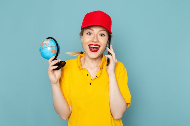 黄色のシャツと青い空間に笑みを浮かべて電話で話している赤いマントの正面若い女性宅配便