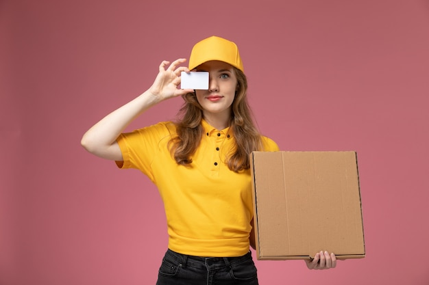 濃いピンクの机の上の茶色の箱と白いカードを保持している黄色の制服を着た若い女性の宅配便の正面図制服配達サービス女性労働者