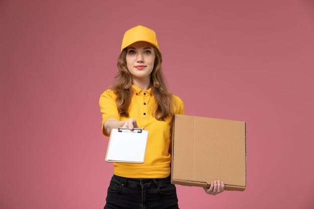 Вид спереди молодая женщина-курьер в желтой форме, держащая коричневую коробку с едой и блокнот на розовом столе, работник службы доставки униформы