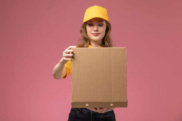 濃いピンクの机の上に茶色のフードボックスを開いている黄色の制服を着た若い女性の宅配便の正面図制服配達サービスの女性労働者