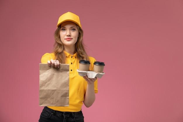 濃いピンクの机の上のコーヒーカップと食品パッケージを保持している黄色の制服を着た若い女性の宅配便の正面図制服配達ジョブサービスワーカー