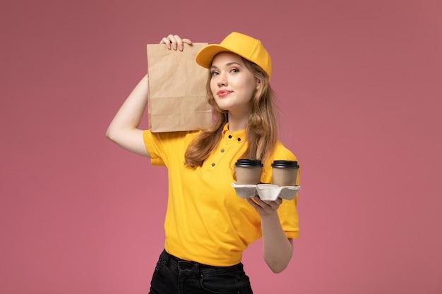 正面図黄色の制服を着た若い女性の宅配便コーヒーカップとピンクの背景の机の上の食品とパッケージを保持している仕事の制服配達サービスワーカー