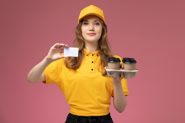 Вид спереди молодая женщина-курьер в желтой форме, держащая кофейные чашки и белую карточку на темно-розовом столе, работник службы доставки униформы