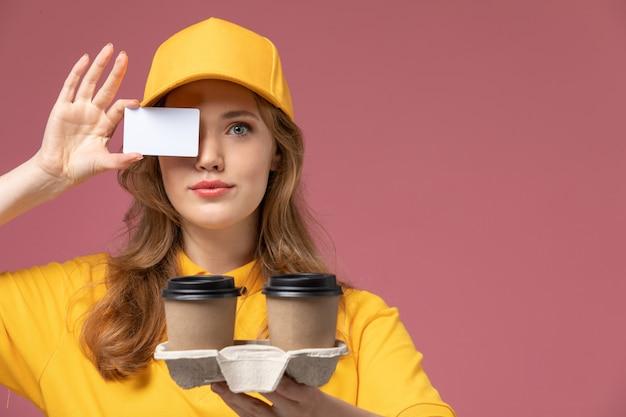 ピンクのデスクの仕事の制服配達サービスワーカーに配達コーヒーと白いカードを保持している黄色の制服を着た若い女性の宅配便の正面図
