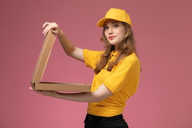 ピンクの背景の仕事の制服配達サービス労働者にそれを開く配達フードボックスを保持している黄色の制服を着た若い女性の宅配便の正面図