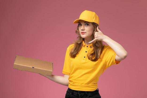ピンクの机の上の配達フードボックスを保持している黄色の制服を着た若い女性の宅配便の正面図仕事制服配達サービス労働者