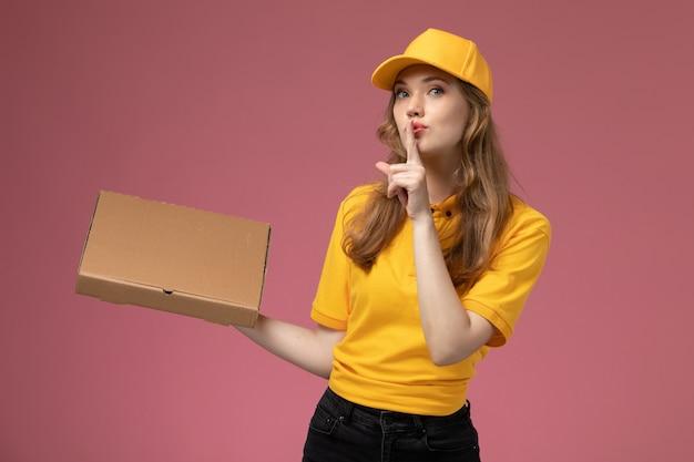 Вид спереди молодая женщина-курьер в желтой форме, держащая посылку с доставкой еды и показывающая знак тишины на розовом столе, работник службы доставки униформы