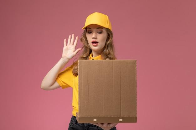 ピンクの机の上の仕事の制服配達サービス労働者でそれを見ている配達食品パッケージを保持している黄色の制服を着た若い女性の宅配便の正面図