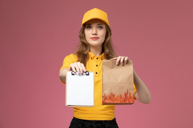 분홍색 배경 작업 유니폼 배달 서비스에 배달 음식 패키지 메모장을 들고 노란색 제복을 입은 전면보기 젊은 여성 택배